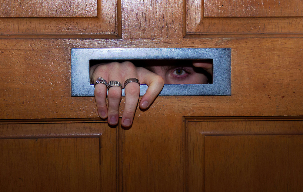 'Coxy' a Cheltenham student stares through an open letter box from behind a closed door during the second UK national lockdown in November 2020. Credit: Katie Sillett-Bradford/UoG/PathosImages