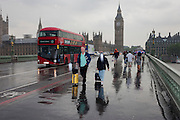 Wet tourists and visitors to London's Southbank, endure heavy summer rainfall on Westminster Bridge, England.