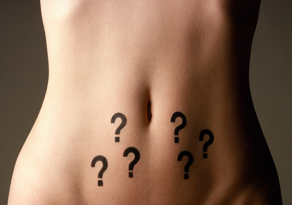 Close up of question marks drawn on a woman's nude stomach