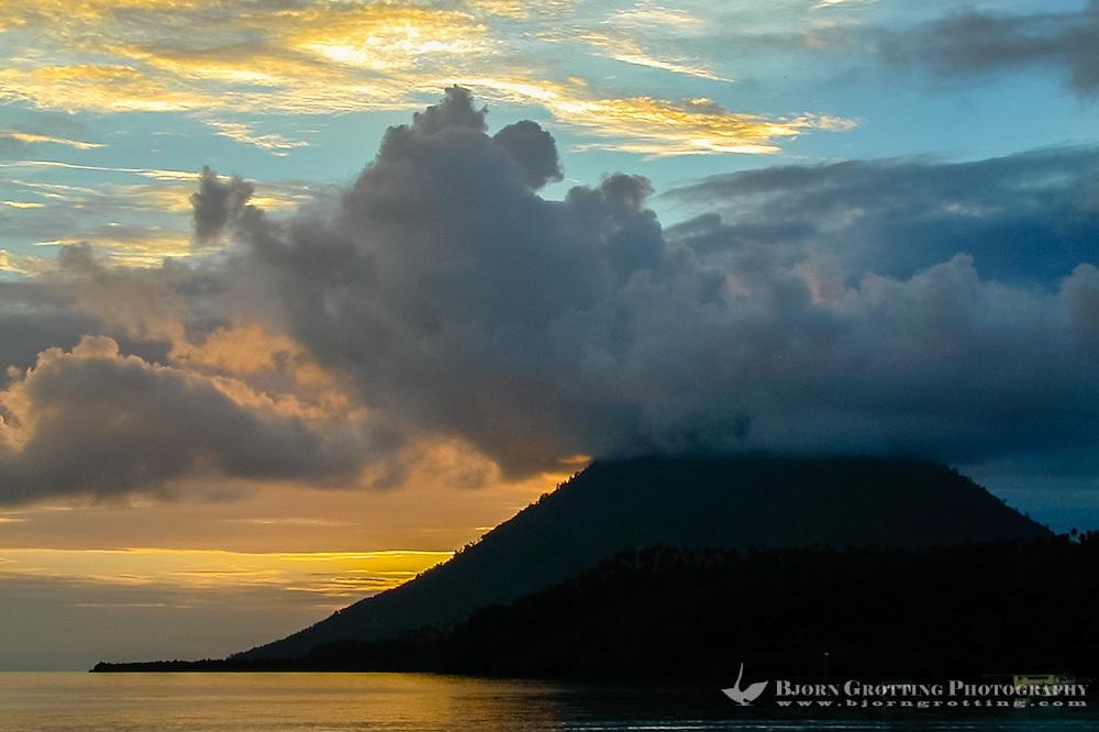 Indonesia, Sulawesi, Bunaken. Sunset at Bunaken. Manado Tua is a landmark with it's characteristic cone shape, a now extinct volcano.