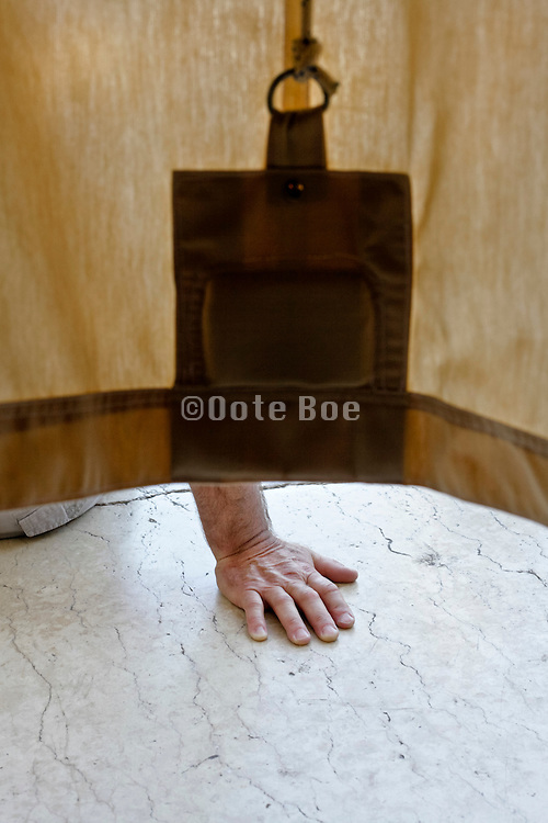 hand sticking out from under a canvas curtain