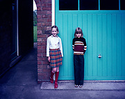 Full length portrait of two young girls standing by domestic garage of home, 1960s or 1970s