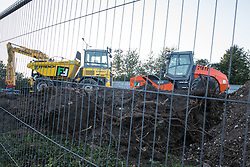Fencing is positioned around heavy machinery and land cleared of trees and undergrowth at the HS2 Buckinghamshire Junctions Laydown Area on 17th July 2020 in Amersham, United Kingdom. The Department for Transport approved the issuing of Notices to Proceed by HS2 Ltd to the four Main Works Civils Contractors (MWCC) working on the £106bn high-speed rail link project in April 2020.