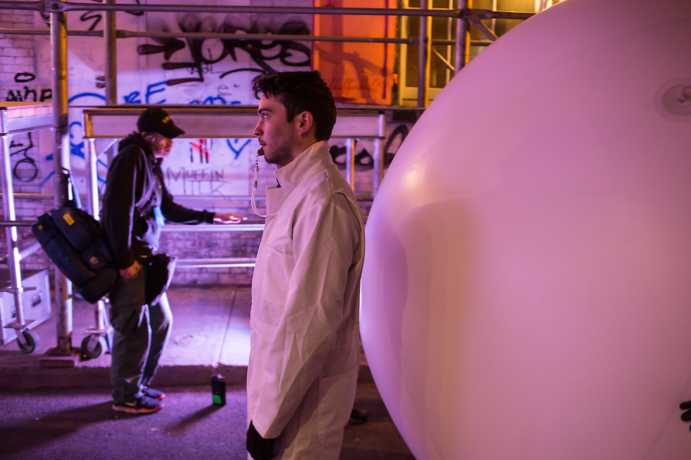 A handler walks slowly in front of an inflated ball on Jersey Street near the corner of Mulberry Street, part of the Ideas City performance by Snarkitecture.