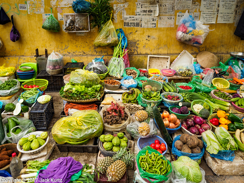 """22 DECEMBER 2017 - HANOI, VIETNAM: A fruit and vegetable stand on the street of the old quarter of Hanoi. The old quarter is the heart of Hanoi, with narrow streets and lots of small shops but it's being """"gentrified"""" because of tourism and some of the shops are being turned into hotels and cafes for tourists and wealthy Vietnamese.    PHOTO BY JACK KURTZ"""