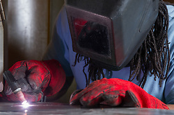 A prisoner welding in a prison workshop making prison beds in HMP Feathstone