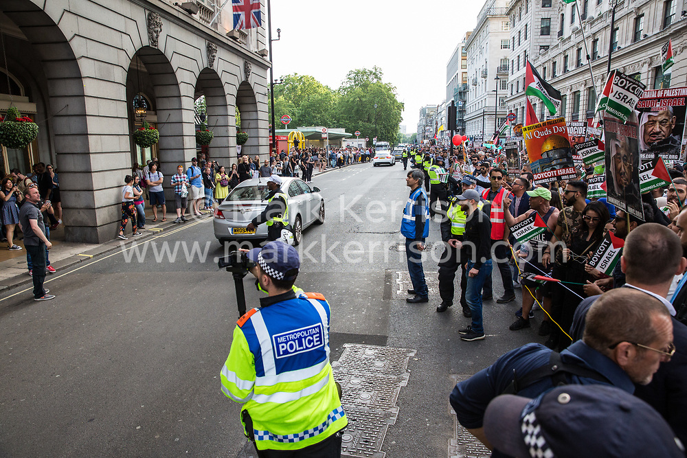 London, UK. 10th June, 2018. A police officer films members of a far-right group taunting hundreds of people taking part in the pro-Palestinian Al Quds Day march through central London organised by the Islamic Human Rights Commission. An international event, it began in Iran in 1979. Quds is the Arabic name for Jerusalem.