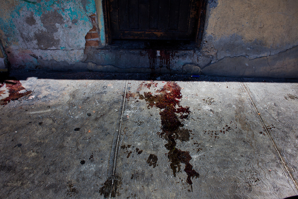 Blood is seen on the doorstep of a home in Ciudad Juarez where three men were executed. According to neighbors the men were low level street drug vendors.