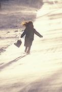 Girl walking down road on windy winter day
