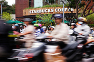 The motorbike is Vietnam's favored mode of transportation, having replaced the bicycle. Here traffic moves in a blur pas a recently opened Starbucks as thousands of motorbikes pass through the busy Saigon intersection every hour. Robert Dodge, a Washington DC photographer and writer, has been working on his Vietnam 40 Years Later project since 2005. The project has taken him throughout Vietnam, including Hanoi, Ho Chi Minh City (Saigon), Nha Trang, Mue Nie, Phan Thiet, the Mekong, Sapa, Ninh Binh and the Perfume Pagoda. His images capture scenes and people from women in conical hats planting rice along the Red River in the north to men and women working in the floating markets on the Mekong River and its tributaries. Robert's project also captures the traditions of ancient Asia in the rural markets, Buddhist Monasteries and the celebrations around Tet, the Lunar New Year. Also to be found are images of the emerging modern Vietnam, such as young people eating and drinking and embracing the fashions and music of the West. His book. Vietnam 40 Years Later, was published March 2014 by Damiani Editore of Italy.