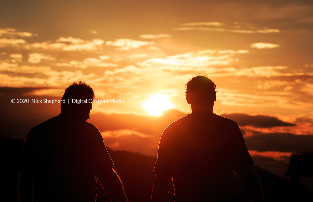 Two farm workers head home at the end of a long day as the sun sets in Croatia.