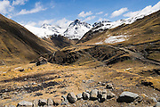 Snow-capped peaks rise above an ancient footpath and a lone shepherd's hut in the community of Q'eros, high in the Cordillera de Paucartambo, Andes Mountains, Peru. The Q'eros, a Quecha people, are considered the last direct descendants of the Incas and proudly maintain many of their ancient traditions.