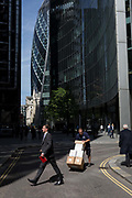 A delivery man and businessman cross paths in the City of London - the capitals financial district, on 6th June 2018, in London, England.