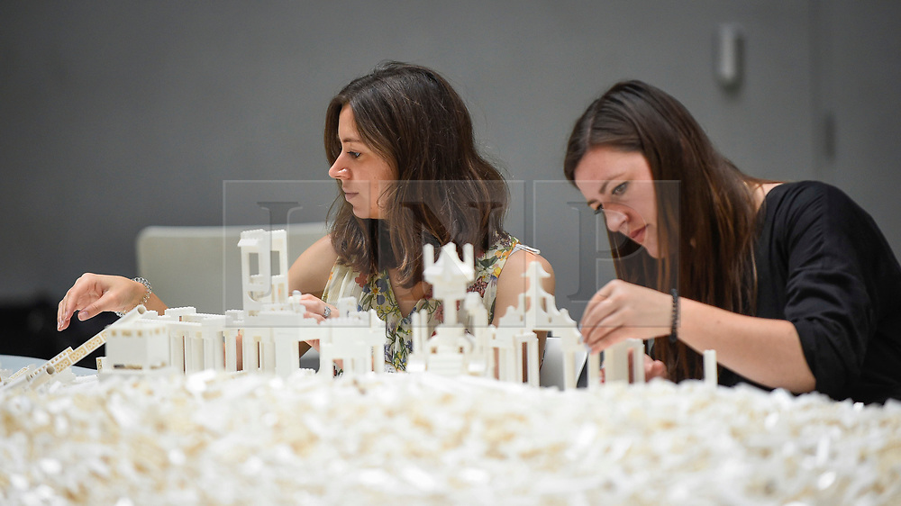 """© Licensed to London News Pictures. 26/07/2019. LONDON, UK. Visitors work with Lego at the preview of """"The cubic structural evolution project"""", 2004, by Olafur Eliasson at Tate Modern.  Exhibited for the first time in the UK, the artwork comprises one tonne of white Lego bricks inspiring visitors to create their own architectural vision for a future city and is on display until 18 August 2019.  The work coincides with the artist's new retrospective exhibition """"In real life"""" at Tate Modern on display to 5 January 2020.  Photo credit: Stephen Chung/LNP"""