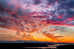 United States, Washington. Lake Washington, Mercer Island, Seattle skyline, and Olympic mountains viewed from Bellevue at sunset.