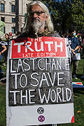 A climate activist stands with a sandwich board in Parliament Square during a Global Climate Strike to demand intersectional climate justice on 24th September 2021 in London, United Kingdom. The Global Climate Strike was organised to highlight the detrimental influences through colonialism, imperialism and exploitation of the Global North on MAPA Most Affected Peoples and Areas, which have contributed to them now experiencing the worst impacts of the climate crisis, and to call on the Global North to pay reparations to MAPA.