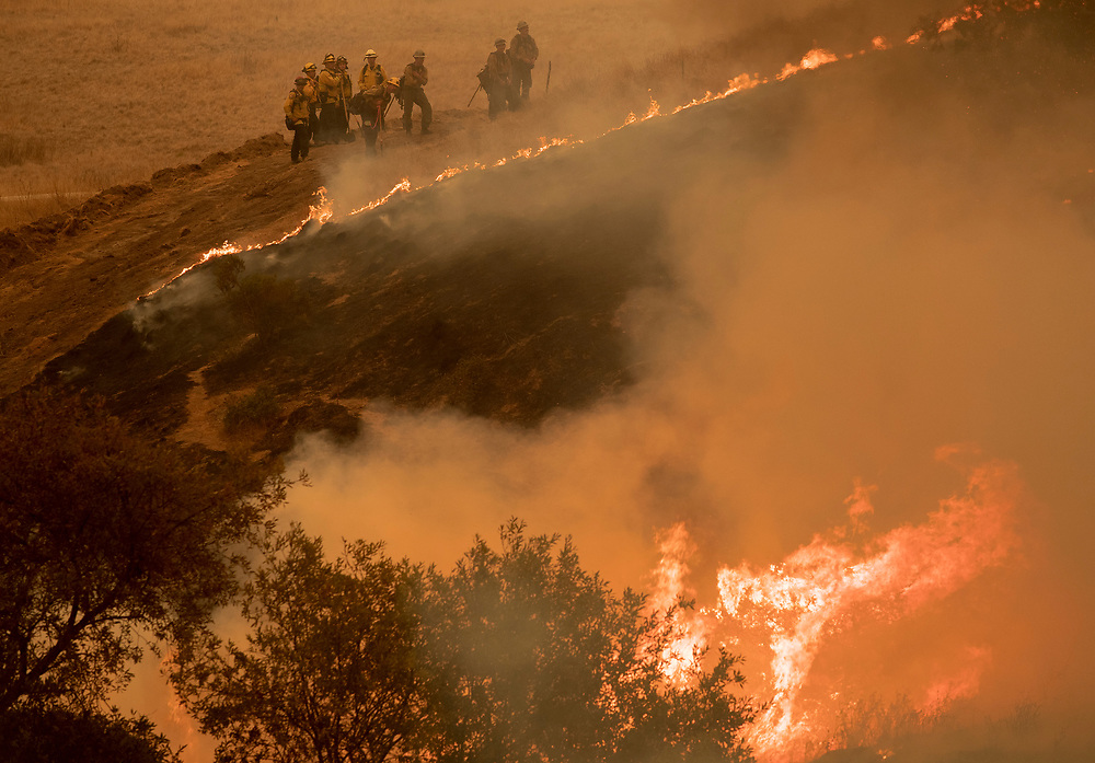 Firefighters monitor a back burn to help slow the River Fire from approaching houses in the Las Palmas neighborhood near Salinas, Calif. on Aug. 19, 2020.