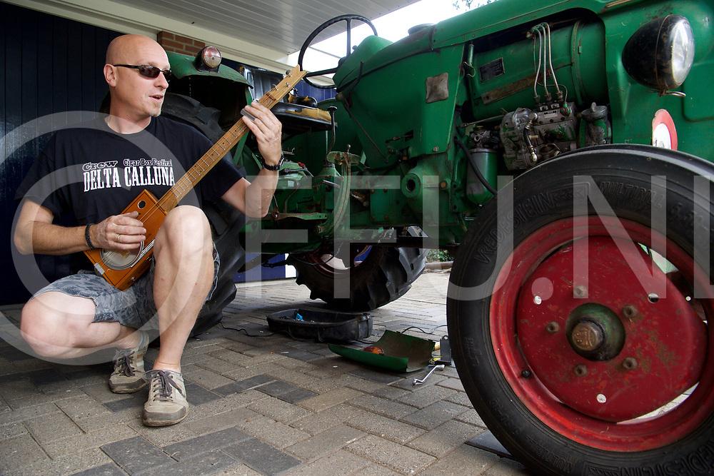 DALFSEN - Cigar box festival.<br /> Foto:  Henri Grootenhuis deelt zijn liefde voor de  Cigar box gitaar met een oude trekker.<br /> FFU Press Agency copyright Frank Uijlenbroek
