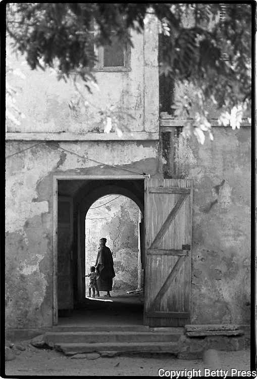 A woman with her child enters her colonial style home on Gorée Island, one of the centers for slave trade in West Africa. Visitors go there to tour the slave museum, a memorial to the atrocities of the slave trade. <br /> Image size 8x12, matted 16x20, edition of 10<br /> <br /> Image size 12x18 matted 20x24, edition of 25<br /> <br /> Silver Gelatin Print