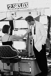 Young man looking at young woman gambling at slot machine