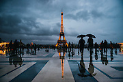 Rainy evening at Place du Trocadero with reflection of people and the Eiffel Tower on the wet ground.