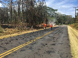 May 6, 2018 - Hawaii, U.S. - At 1:24 p.m. HST, May 6, 2018, USGS scientists monitoring the eruption in Leilani Estates walk past spatter that was erupted from fissure 5-6 on Leilani Avenue. Homes destroyed by Hawaii's Kilauea volcano has climbed to at least 30. Lava has been spewing more than 200 feet in the air. More than 1,700 people evacuated. (Credit Image: ? USGS/ZUMA Wire/ZUMAPRESS.com)