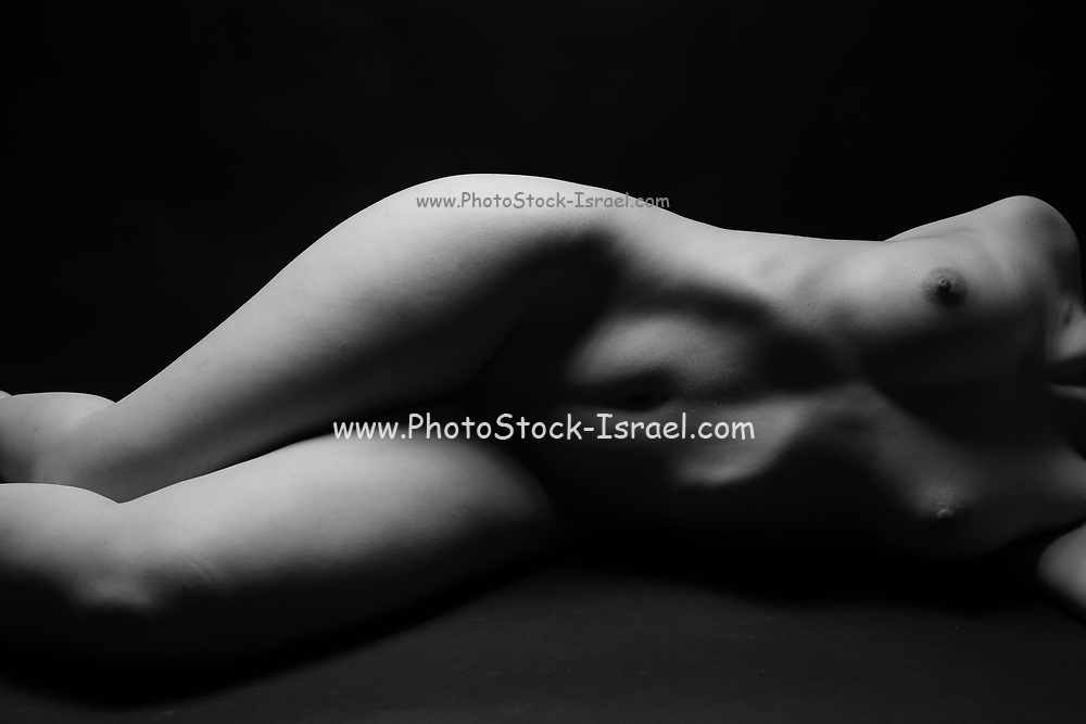 Artistic female nude photography with emotive lighting front view on black background