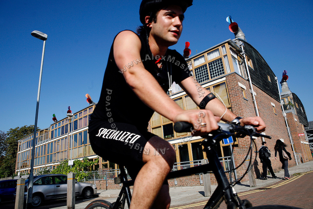 Matt Mellen, 27, a project coordinator for One Planet Living, a Peabody Trust partner organisation, is arriving at work at the BedZED housing complex with his bike, on Thursday, Sep. 6, 2007, in London, UK. BedZED or the Beddington Zero Energy Development, is an environmentally-friendly housing development near Wallington, England in the London Borough of Sutton. It was designed by the architect Bill Dunster who was looking for a more sustainable way of building housing in urban areas in partnership between the BioRegional Development Group and the Peabody Trust. There are 82 houses, 17 apartments and 1,405 square meters of work space were built between 2000. The project was shortlisted for the Stirling Prize in 2003. The project is designed to use only energy from renewable source generated on site. In addition to 777 square meters of solar panels, tree waste is used for heating and electricity. The houses face south to take advantage of solar gain, are triple glazed and have high thermal insulation while most rain water is collected and reused. Appliances are chosen to be water efficient and use recycled water wherever possible. Low impact building materials were selected from renewable or recycled sources and were all originating within a 35 mile radius of the site to minimize the energy required for transportation. Also, refuse collection facilities are designed to support recycling and the site encourage eco-friendly transport: electric and LPG cars have priority over petrol/diesel cars, and electricity is provided by parking spaces appositely built for charging electric cars.