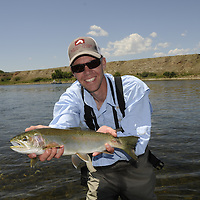 Smiling angler with rainbow trout in hand