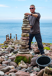 Dunbar, East Lothian, Scotland, United Kingdom 10 July 2021. European Stone Stacking Championship: The first day of the event, which is part of the Edinburgh Science Festival.  Pictured: a competitor in the most stones stacked in half an hour competition. The record is 42.<br /> Sally Anderson | EdinburghElitemedia.co.uk