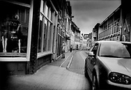 Sex worker outside her glass-fronted booth on one of two roads where prostitution is permitted in Groningen as a car, driven by a man, very slowly proceeds past the booths as potential customers do throughout the day and night.  The Netherlands.  Although prostitution is legal in the Netherlands, young men of Eastern European origin stand guard at the ends of alleyways carefully watching the activities of the young women.  Although the nationality of this particular woman is not known, many of the sex workers in the Netherlands are from Eastern Europe.