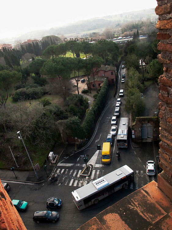 Rome, Aurelian walls from an embrasure at the top of the San Sebastiano gate, looking along the Appian Way as a bus turns to enter it.