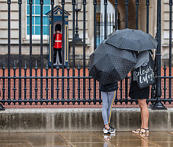 © Licensed to London News Pictures. 19/08/2020. London, UK. Tourists get caught in heavy rain with gusty winds outside Buckingham Palace in Westminster today as weather forecasters predict a warmer and sunnier week ahead with highs of 24c . Photo credit: Alex Lentati/LNP