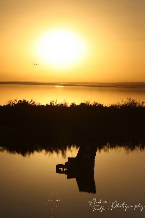 Andrew Foulk/For High Country News.A lounge chair sit in a lagoon next to the sea as the sun makes its final presence over the sea.