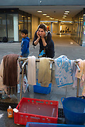 Refugees, Keleti station Budapest, Hungary. A refugee woman has a wash at a tap stand.