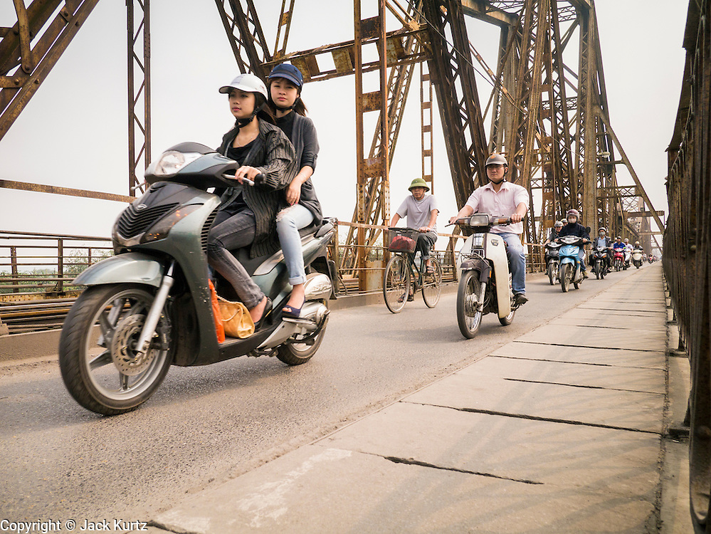 02 APRIL 2012 - HANOI, VIETNAM: Commuters ride their bikes and motorcycles on the Long Bien Railraod Bridge over the Red River into Hanoi, the capital of Vietnam. The bridge was built by the same architect who designed the Eiffel Tower. Most of the original spans over the river were detroyed by American bombers that repeatedly attacked Hanoi during Vietnam's war with the US.      PHOTO BY JACK KURTZ