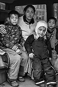 A Roma feamle beggar from Romania sit with three of her children in the family minibus in a parking lot in Uppsala, Sweden. The children are looked after by the father while the mother begs in the streets of the town during the day.
