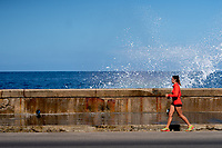 Runner being splashed on the Malecon, Havana, Cuba 2020 from Santiago to Havana, and in between.  Santiago, Baracoa, Guantanamo, Holguin, Las Tunas, Camaguey, Santi Spiritus, Trinidad, Santa Clara, Cienfuegos, Matanzas, Havana