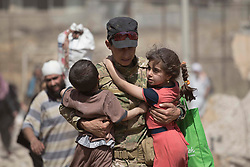 © Licensed to London News Pictures. 15/06/2017. Mosul, Iraq. An Iraqi Army soldier, of 9th Armoured Division, holds two children as they and their family flee from ISIS held West Mosul.<br /> <br /> Despite heavy fighting between the Islamic State and Iraqi Security Forces many civilians have started to leave ISIS territory in West Mosul. Mosul residents, many of whom have been in hiding in their homes since the start of the West Mosul Offensive, often have to run through ISIS sniper and machine gun fire to reach the safety of Iraqi Security Forces positions. Photo credit: Matt Cetti-Roberts/LNP