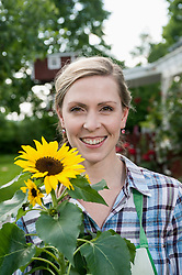 Portrait woman holding sunflower smiling