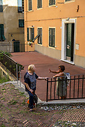 Two women chat on a street corner in the morning sunshine. Genoa, Italy.
