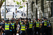 Protesters who have been trapped by police for processing during the Melbourne Freedom Rally at Parliament House. Police move into position on the steps of state parliament ahead of a planed protest. The groups who have organised the many Freedom Day protests over the last 3 months, attempted to march on State Parliament during Melbourne Cup Day demanding the sacking of Premier Daniel Andrews for the lockdown and attacks on their civil liberties. Police met with the protester's with significant force despite the city having had zero cases for five days. (Photo by Dave Hewison/Speed Media)