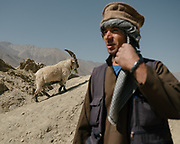 Tajik man of Wakhi origin posing as an Afghan for paid picture opportunities. The ancient Qaqa Fortress ruins near Namadgud village. <br /> Trekking between Namadgud village and Ishkashim town. Sights and places to see while walking along the Tajikistan side of the Wakhan Corridor.