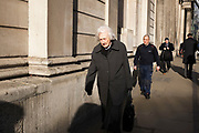Elderly woman walking past the Bank of England in the City of London, UK. In old age she appears to be very sprightly.