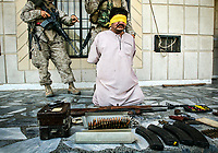 Ramadi, Iraq -- 1st Battalion/5th Marines, Bravo Company Marines document weapons and a detainee along with other evidence found during a search of a home in Ramadi, Iraq and detaining the man living there. -- Photo by Jack Gruber, USA TODAY