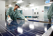 Workers make final inspection on solar panels at the Suntech Power Holdings factory in Wuxi, Jiangsu Province, China on 28 July 2009.  While China, the world's largest electricity consumer, installed less that 3% of the world's solar power capacity last year, its government subsidized alternative energy manufacturing industry now supplies the majority of the solar panels on the world market.