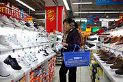 A woman browses for shoes at a Carrefour supermarket in Shanghai, China on 11 January 2010.  Carrefour has one of the strongest presence as a foreign retailer in China.