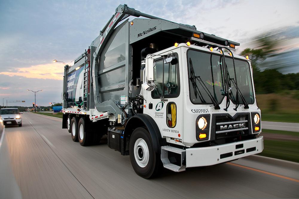 Front Loader Waste Disposal Truck speeding down highway showing motion