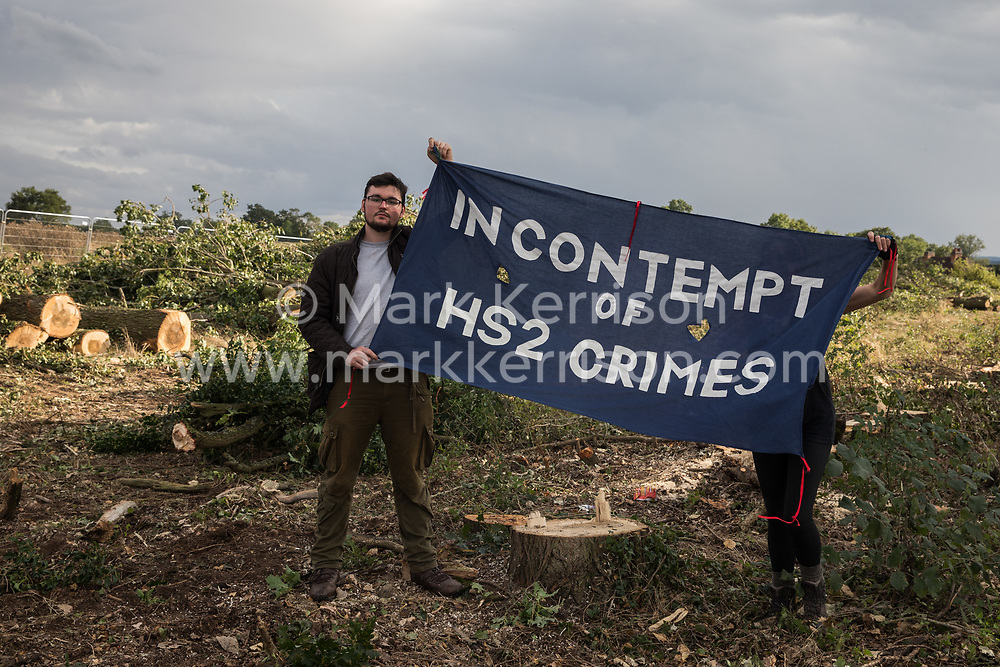 Offchurch, UK. 24th August, 2020. Anti-HS2 activists hold a banner in front of felled trees alongside the Fosse Way. Environmental activists based at wildlife protection camps in Warwickshire have been trying to prevent or delay the felling of large numbers of trees in connection with the £106bn HS2 high-speed rail link, which will destroy or significantly impact many irreplaceable natural habitats including 108 ancient woodlands.