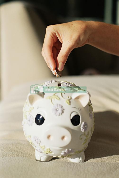 Dec. 14, 2012 - Putting money in a piggy bank (Credit Image: © Image Source/ZUMAPRESS.com)